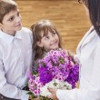 Boy and girl children give flowers as a school teacher in teache — Stock Photo #79231220