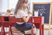 Little girl sitting on the chair and on the books at school in c — Stock Photo