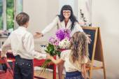 男の子と女の子の子供が先生に学校の先生としての花を与える — ストック写真
