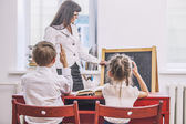 Boy and girl children with the teacher in the school has a happy — Stock Photo