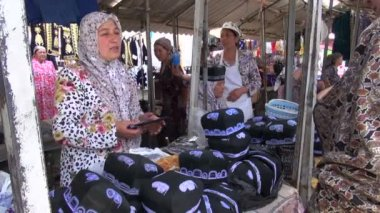 A woman is selling male muslim skullcaps — Stock Video