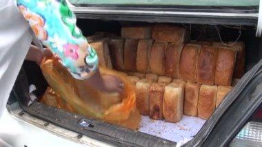 Женщина принимает хлеба из автомобиля — Стоковое видео