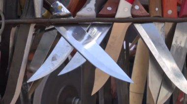 A man is sharpening knives at the bazaar. — Stock Video