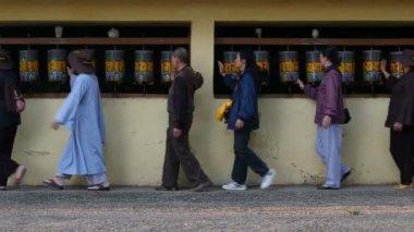 Devotees walk past prayer wheels — Stock Video