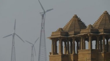 Windmills turn behind the tower of temple — Stock Video