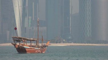 A dhow vessel in front of the business district — Stok video