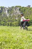 Female cyclist traveling on a bicycle with a load. — Stock Photo