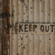 Keep out - handwritten sign on a closed rustic weathered door — Stock Photo #75758823