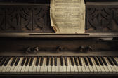 Old piano wtith pge of notes — Stock Photo