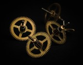 Group of gold metal gearwheels on black background — Stock Photo