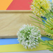 Green, white and yellow artificial flower on orange, red, blue and green background give romantic look concept with two ladybird and cropped brown wood on left — Stock Photo #79325026