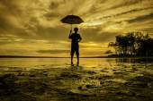 Image silhouette a boy standing holding an umbrella during sunset sunrise. sand and tree with soft cloud on sky — Stock Photo