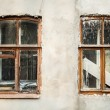 Wrecked white stucco wall with two wooden windows covered in whi — Stock Photo #69340365