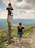 Туристический женщина стоя и видом на пост с информацией — Стоковое фото