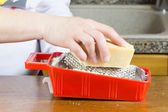 Grating Parmesan cheese — Stock Photo