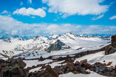 Snow on the mountains against the blue sky in the clouds.The Elbrus region.The Caucasus. — Stock Photo