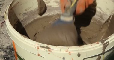 Construction. Man takes mortar from bucket with trowel. Close-up. — Stock Video
