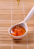 Honey dripping in a wooden spoonful — Stock Photo