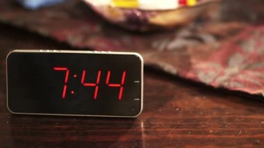 Close-up of a digital clock placed on wooden table when the time's passing — Stock Video