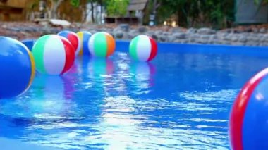 Colorful beach balls floating in pool — Stock Video