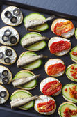 Crostini with anchovies, olives, cucumber, goat cheese — Stock Photo