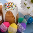 Kulich, traditional Russian Ukrainian Easter cake with colored eggs and flowers — Stock Photo #69465095