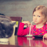 Постер, плакат: Cat and little girl drinking milk