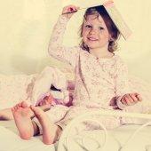 Hermosa niña en la cuna con un libro en la cabeza. — Foto de Stock