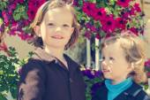 Little girls (sisters) on a background of flowers. — Stock Photo