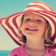 Beautiful little girl in the striped hat on the beach. The image — Stock Photo #77040881