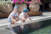Funny little girls (sisters) are playing near the pool. — Stockfoto