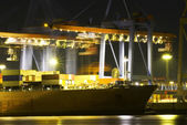 Large container ship in a busy dock at night — Stock Photo