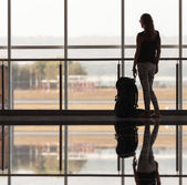 Woman carries your luggage at the airport terminal — Stock Photo