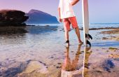 Surfer with surfboard on a coastline — Stock Photo