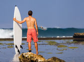 Surfer with surfboard on a coastline — Foto Stock