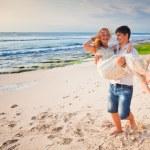 Happy honeymooners couple at the beach — Stock Photo #76500389