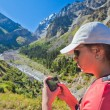 Girl-traveler using mobile in the mountains. — Stock Photo #79721508