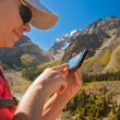 Girl-traveler using mobile in the mountains. — Stock Photo #79721638
