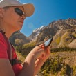 Girl-traveler using mobile in the mountains. — Stock Photo #79721642