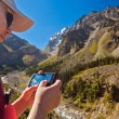Girl-traveler using mobile in the mountains. — Stock Photo #79721646