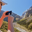 Girl-traveler using mobile in the mountains. — Stock Photo #79721700