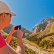 Girl-traveler using mobile in the mountains. — Stock Photo #79721718