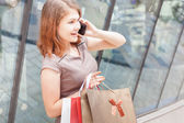 Happy fashion woman with bag using mobile phone, shopping center — Stock Photo