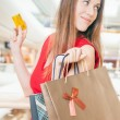 Fashion successful woman holding credit card and bags, shopping mall — Stock Photo #80724390