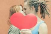 Happy couple kissing and holding heart at red wall background — Stock Photo