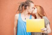 Fashion teenagers couple kissing and holding frame at red background — Стоковое фото