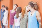 Medium group ofpeople kissing and standing near red wall background — Stock Photo