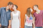 Small group of people kissing, standing near red wall background — Stock Photo