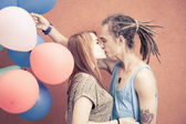 Happy and funny couple kissing at background of color balloons — Stock Photo