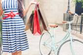 Fashion woman with bags and bike, shopping travel to Italy — Stock Photo